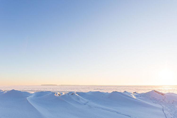 Winter landscape, snowy hills, frozen sea, lots of blue sky, sunrise or sunset.