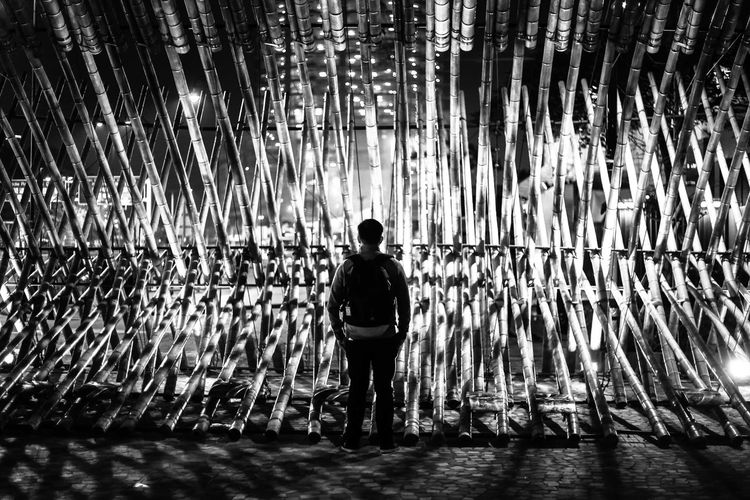 Rear view full length of man standing against illuminated bamboo art at night