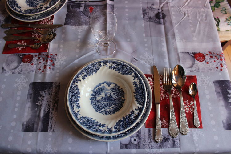 High angle view of crockery by kitchen utensils on table