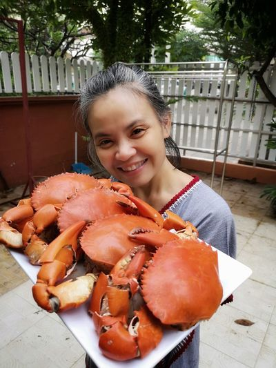 Portrait of smiling woman holding crabs in tray at yard