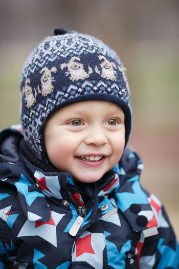 Smiling boy in warm clothes looking away