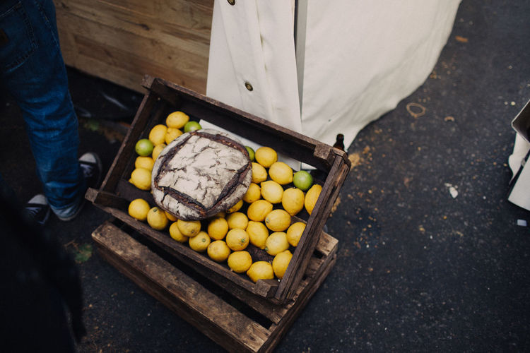 Low Section Of Man Standing By Crate With Lemons