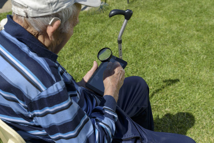 Senior man looking through magnifying glass while using mobile phone in backyard