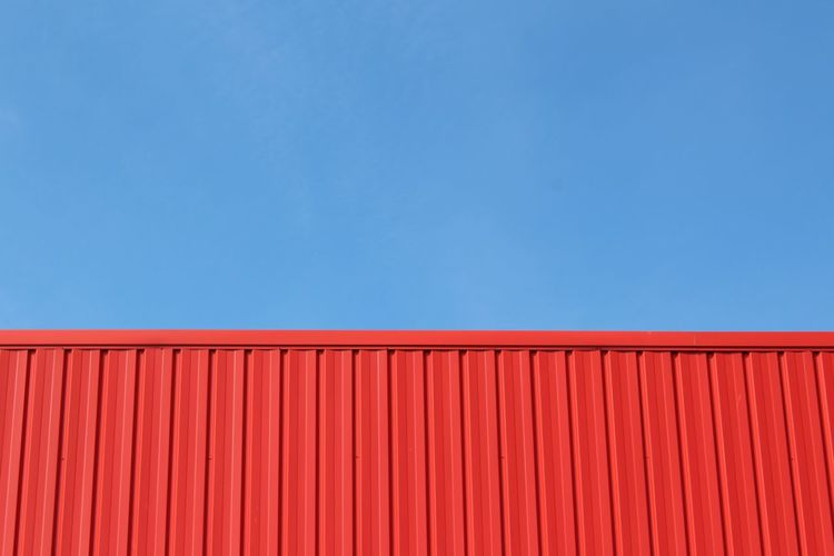 Red building structure against blue sky