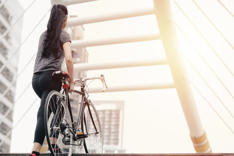 Low angle view of woman riding bicycle