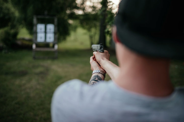 Young man with hat holding gun and shooting to target in countryside at daylight. rear view