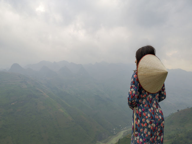 Young Vietnamese women facing and pose for camera with stunning view of the Nho Que river surrounded by mountains from the Ma Pi Leng pass in northern Vietnam Mountain Cloudy Green Color Meo Vac Vietnam Vietnamese Adult Ao Dai Beauty In Nature Casual Clothing Cloud - Sky Environment Hair Hairstyle Landscape Leisure Activity Lifestyles Looking At View Mountain Mountain Range Nature Non-urban Scene One Person Outdoors People Pose Real People Rear View Scenics - Nature Sky Standing Sunrise Three Quarter Length Traditional Dress Tranquility Valley Women
