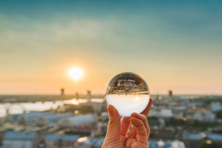 Cropped image of hand holding crystal ball against city