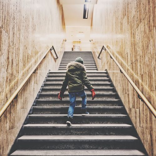 Rear view of boy walking on stairs