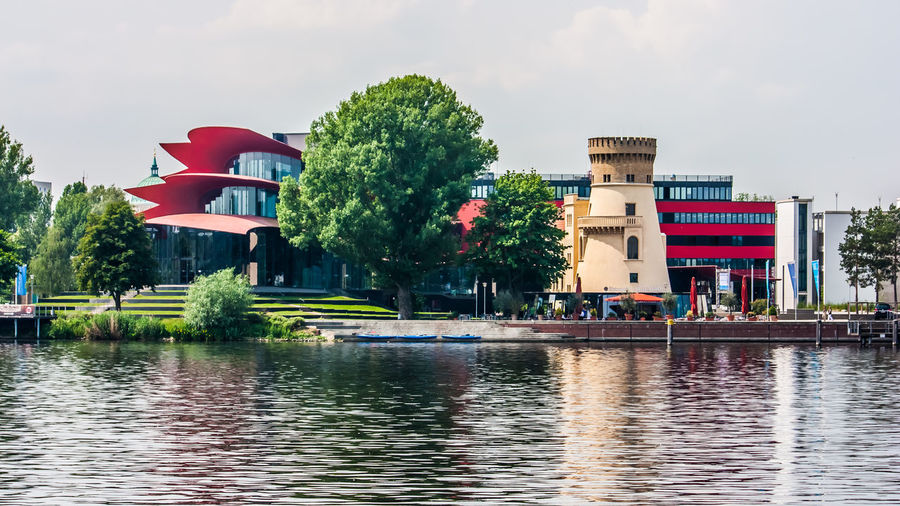 Building by lake against sky in city