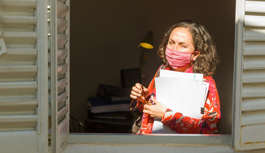 Woman working in office, from a window