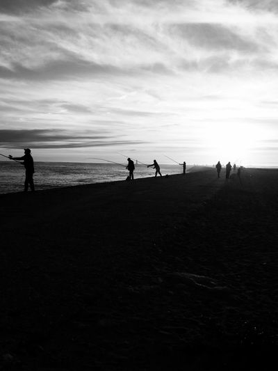 Silhouette people on beach against sky