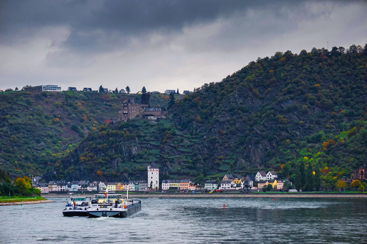 Boat on rhine river by town against mountains