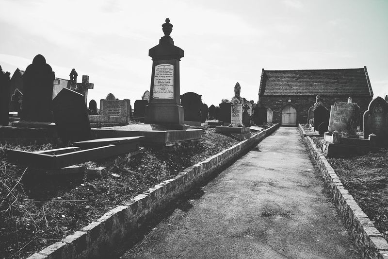 Footpath amidst tombstones at cemetery