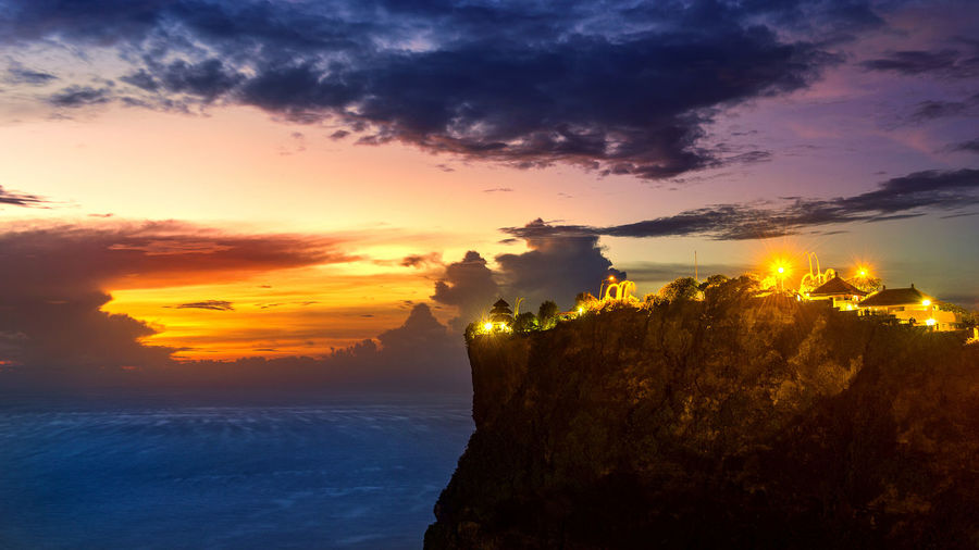 Uluwatu temple on cliff by sea against sky during sunset