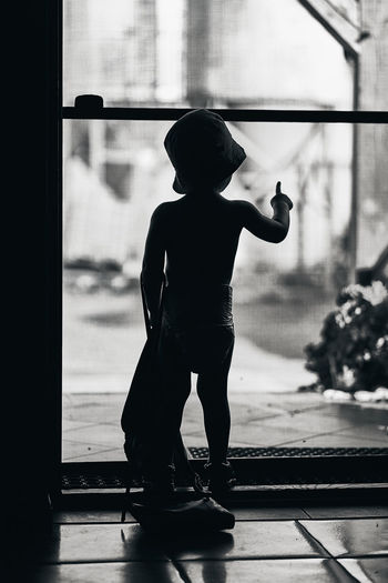 Rear view of silhouette boy standing by window