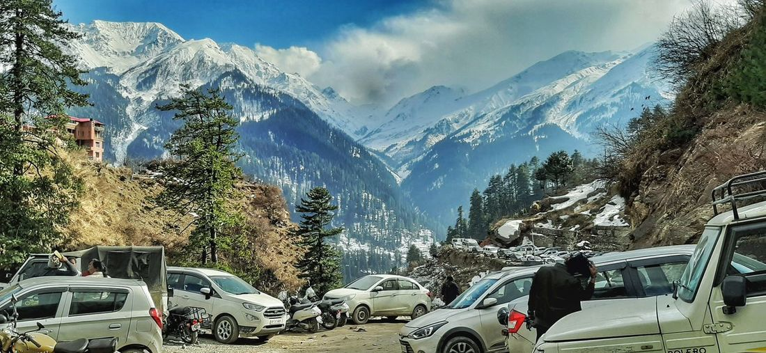 Cars on snowcapped mountains against sky