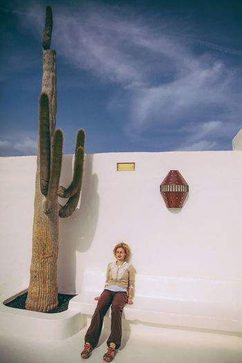 Woman Sitting On Seat By Saguaro Cactus Against Wall