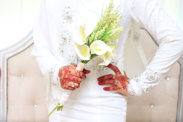 Midsection Of Bride Hands With Henna Tattoo And Bouquet During Wedding