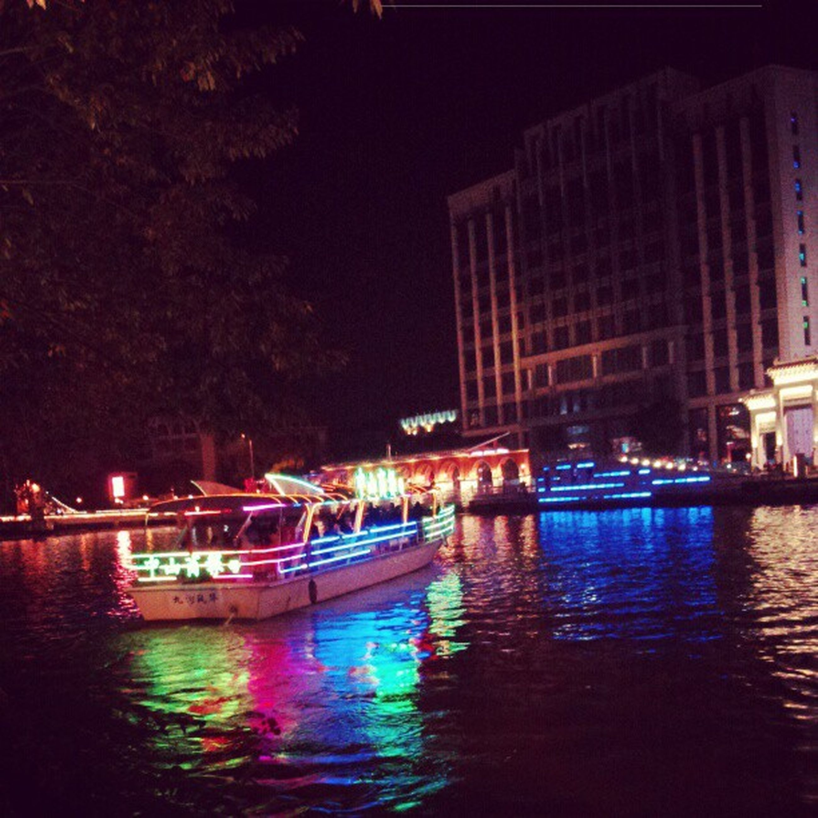 water, waterfront, illuminated, building exterior, architecture, built structure, night, reflection, nautical vessel, boat, transportation, river, moored, mode of transport, city, canal, residential structure, building, sky, clear sky