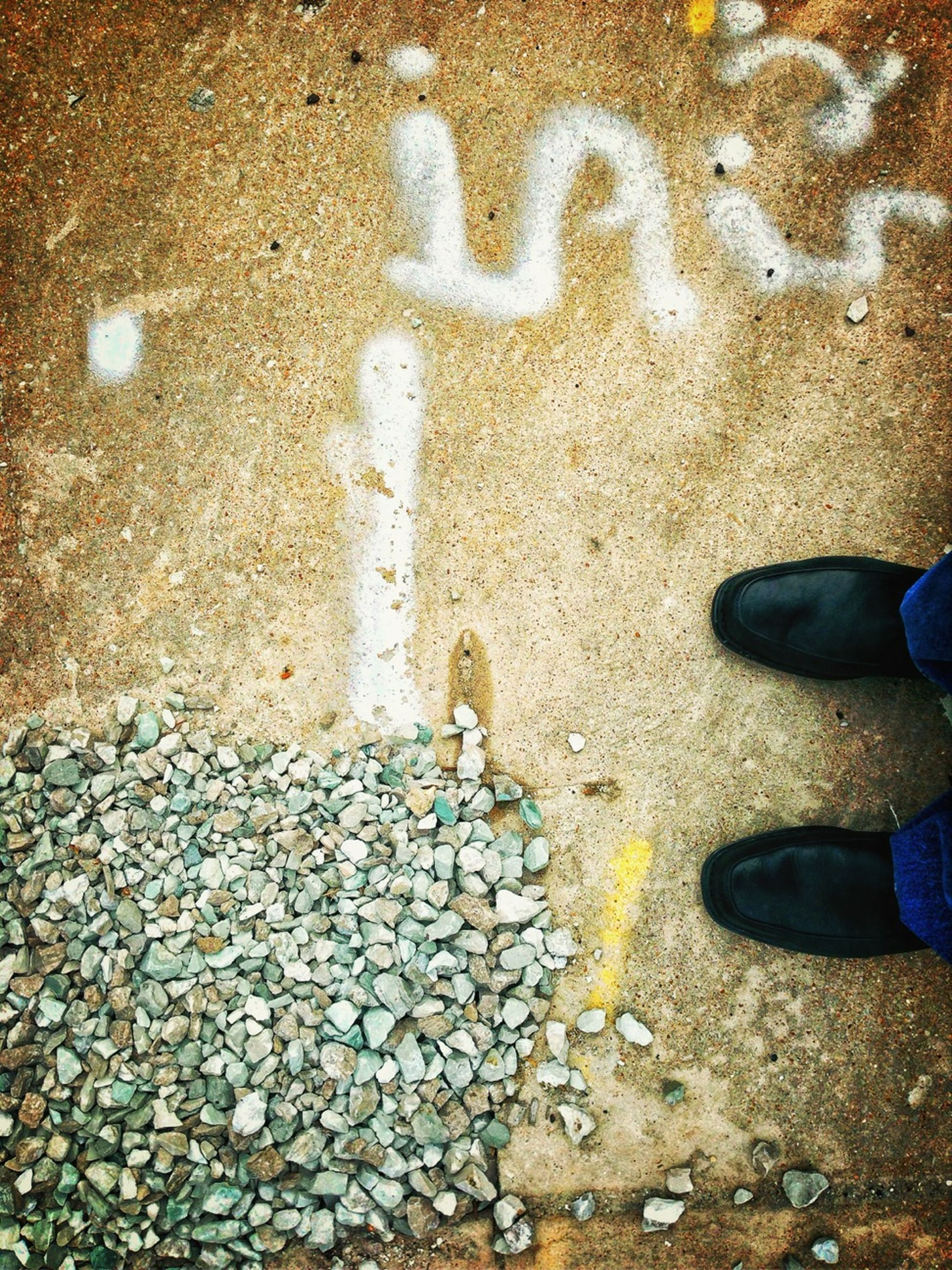 high angle view, low section, street, asphalt, text, person, shoe, standing, textured, stone - object, personal perspective, outdoors, lifestyles, human foot, beach, day, communication