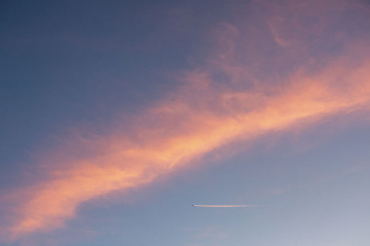 Cloud - Sky Sky Vapor Trail Low Angle View Air Vehicle No People Airplane Beauty In Nature Nature Mode Of Transportation Transportation Scenics - Nature Flying Sunset Outdoors Day Travel Tranquil Scene Orange Color Tranquility