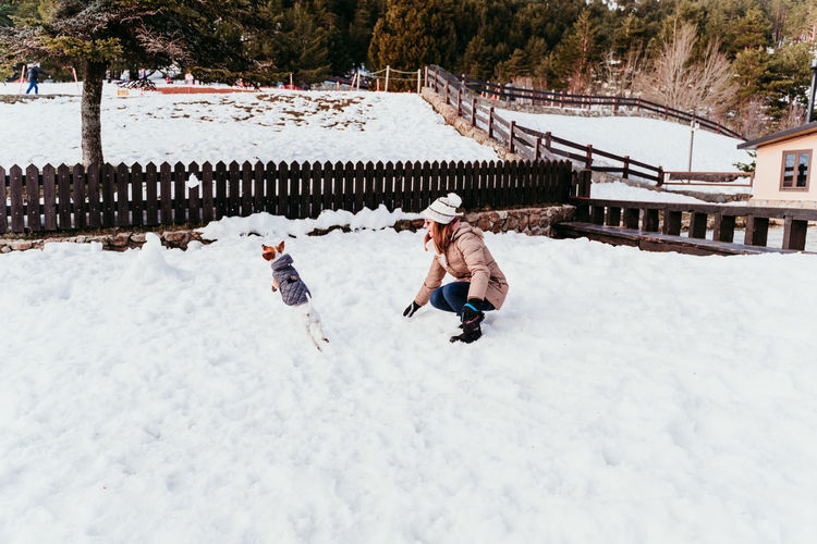 Woman playing with dog on snow covered field