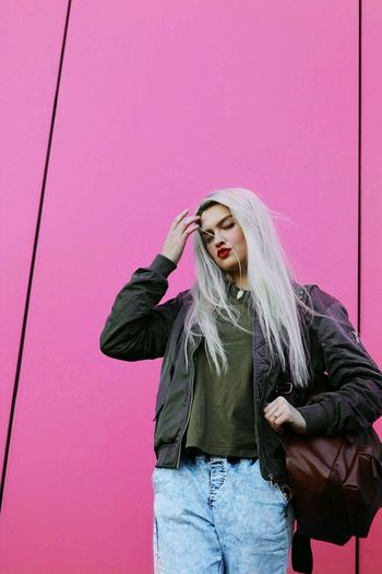 Young Woman Standing Against Pink Wall