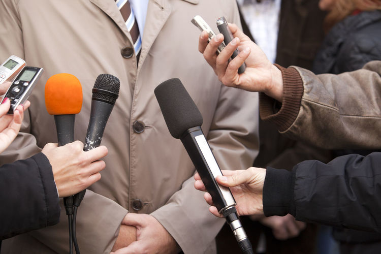 Midsection of politician giving interview while journalists holding microphones