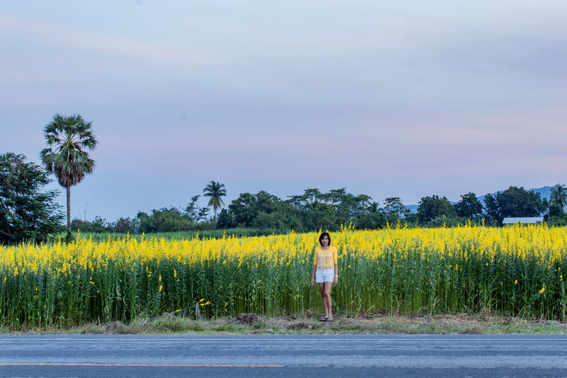 Portrait of woman standing against yellow flowering plants