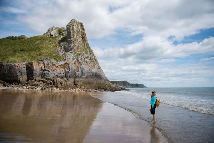 Woman standing by rock on beach