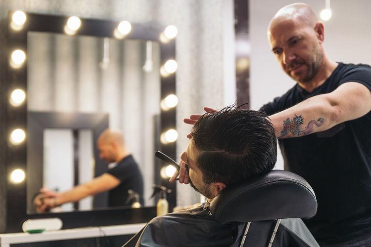 Barber shaving beard in salon