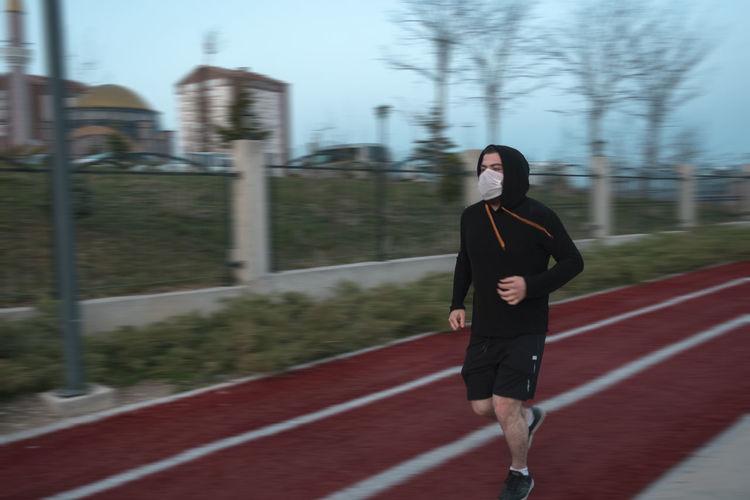 Full length of man wearing mask running in park