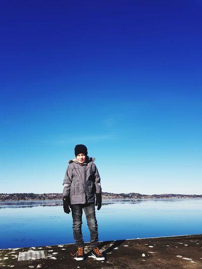 Full length of boy standing on pier against sky