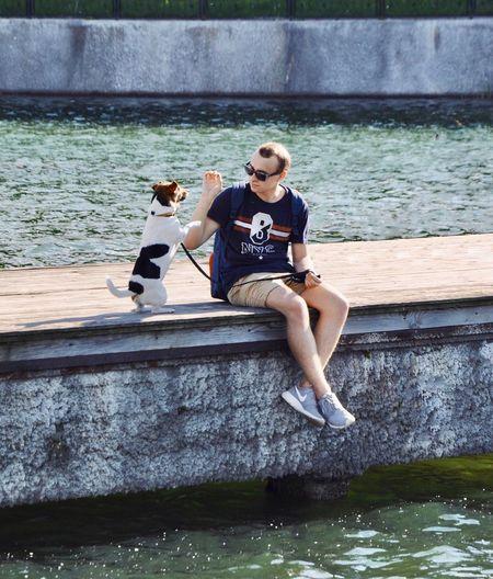 Full length of man sitting on riverbank