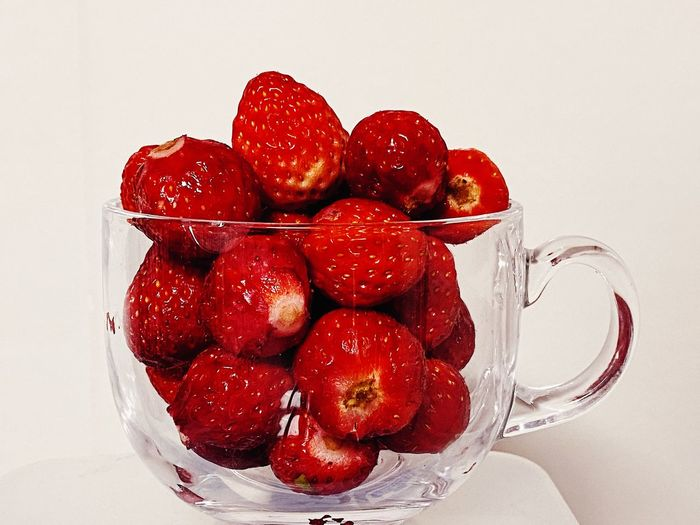 Close-up of strawberries on table against white background