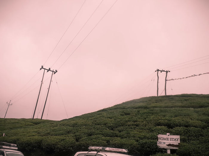 Electricity pylon by mountain against sky