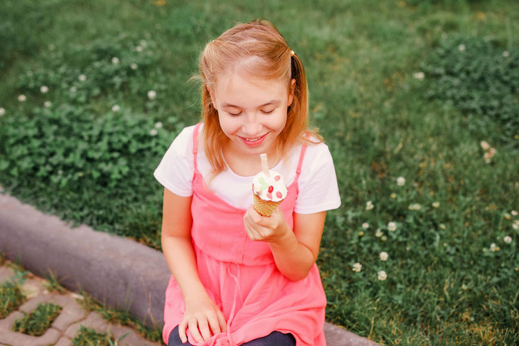 Smiling girl eating food while sitting outdoors