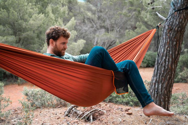 Man sitting on hammock in forest
