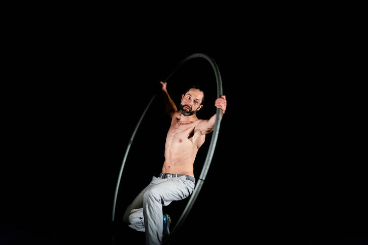 Circus Adult Arts Culture And Entertainment Black Background Copy Space Exercising Front View Full Length Healthy Lifestyle Indoors  Lifestyles Motion One Person Performance Real People Shirtless Skill  Strength Studio Shot