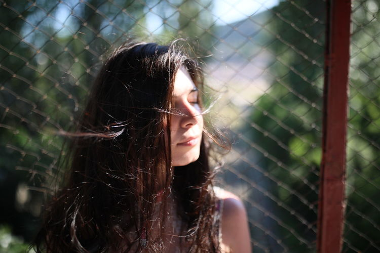 Beautiful woman with eyes closed against chainlink fence