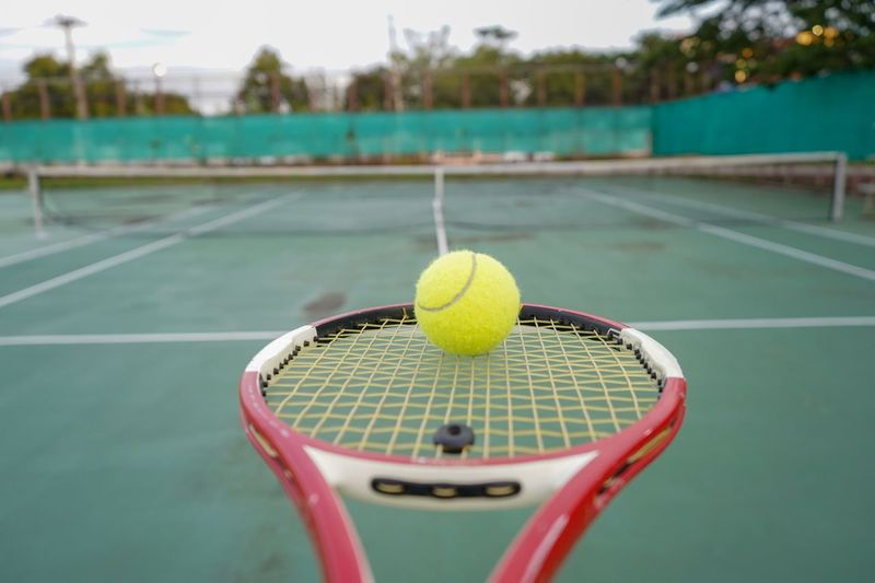 Close-up of tennis ball and racket at court