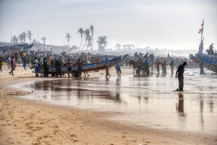 Huge activity on the biggest fisher port of Senegal Group Of People Crowd Large Group Of People Water Real People Beach Land Sky Day Nature Men Adult Transportation Women Outdoors Leisure Activity Lifestyles Holiday