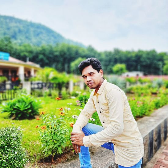 An indian young man standing in the park.