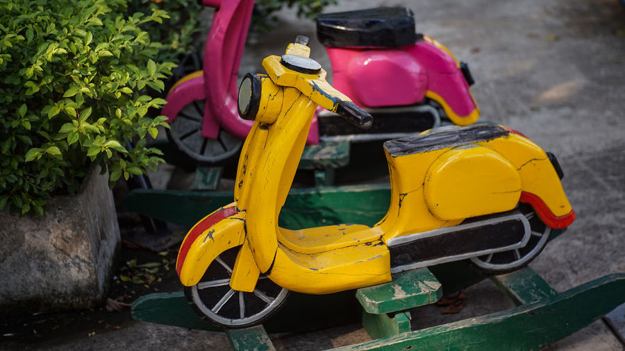 Close-up of yellow motor scooter on road