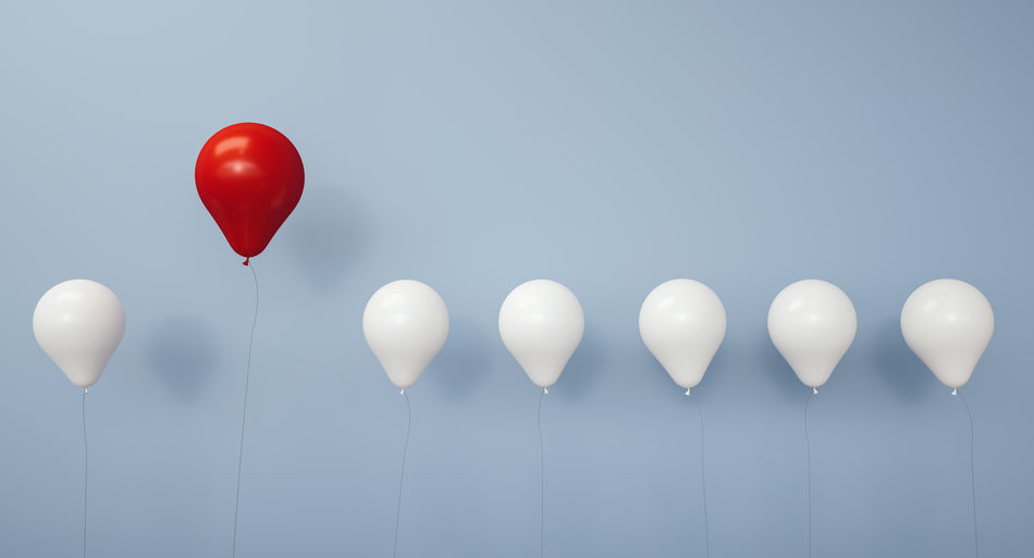 Red and white balloons against gray background