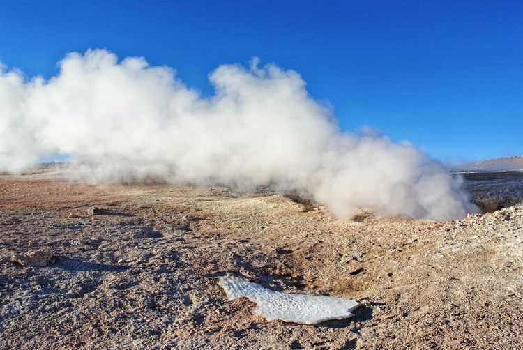 Smoke emitting from volcanic landscape against sky