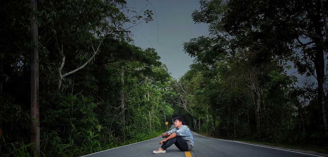 Side view of man on road amidst trees