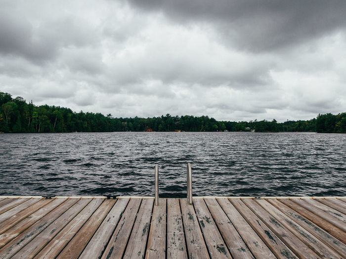 Pier on lake against cloudy sky