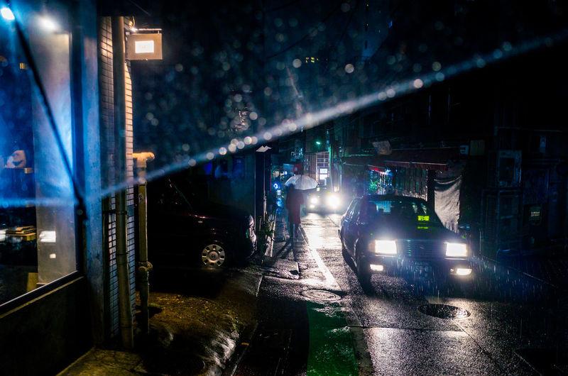 Illuminated Car Headlight On Street During Rainfall At Night